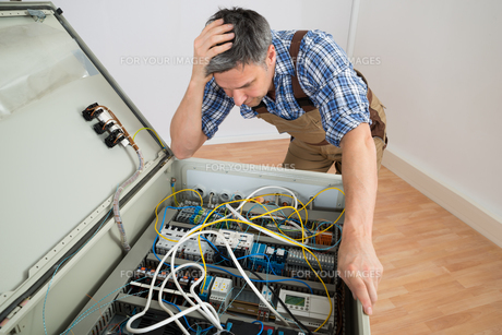 Confused Electrician Looking At Fuse Boxの写真素材 [FYI00646725]