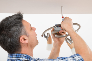 Electrician Fixing Light On Ceilingの写真素材 [FYI00646751]
