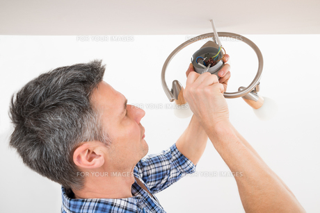 Electrician Fixing Light On Ceilingの写真素材 [FYI00646755]