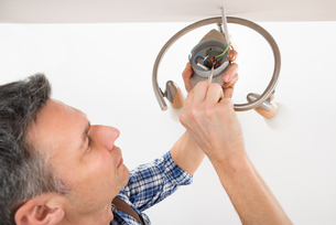 Electrician Fixing Light On Ceilingの写真素材 [FYI00646757]