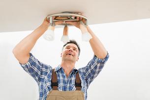 Technician Fixing Light On Ceilingの写真素材 [FYI00646758]