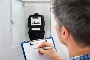 Technician Taking Reading Of Electric Meterの写真素材 [FYI00646759]