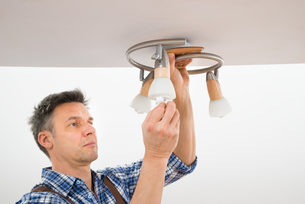 Technician Fixing Light On Ceilingの写真素材 [FYI00646760]