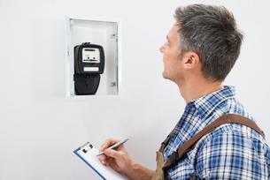 Technician Taking Reading Of Electric Meterの写真素材 [FYI00646761]