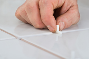 Person's Hand Placing Spacers Between Tilesの写真素材 [FYI00646764]