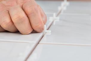 Person's Hand Placing Spacers Between Tilesの写真素材 [FYI00646765]
