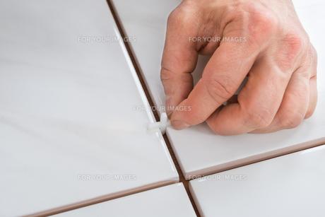 Person's Hand Placing Spacers Between Tilesの写真素材 [FYI00646771]