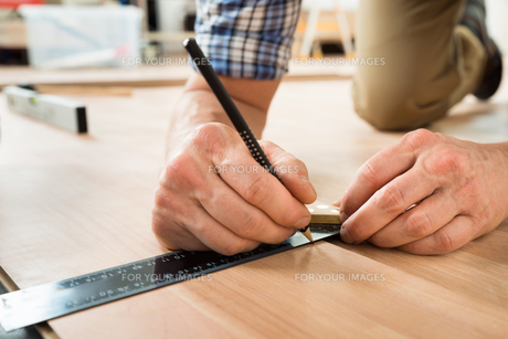 Worker Drawing A Mark On Laminate Using Rulerの写真素材 [FYI00646789]
