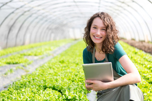 Portrait of an attractive farmer in a greenhouse using tabletの写真素材 [FYI00646829]