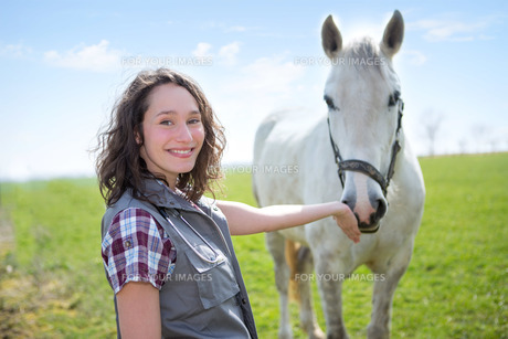 Portrait of a young attractive veterinary in fields with horseの素材 [FYI00646845]
