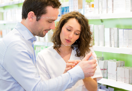 Attractive pharmacist advising a customerの素材 [FYI00646866]