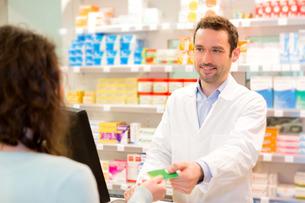 Attractive pharmacist taking healt insurance cardの写真素材 [FYI00646895]