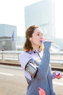 Woman drinking water during a running sessionの写真素材 [FYI00646929]