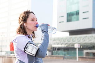 Woman drinking water during a running sessionの写真素材 [FYI00646945]