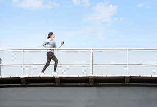 Young attractive woman running on a bridgeの写真素材 [FYI00646970]
