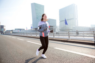 Young attractive woman running downtownの写真素材 [FYI00646994]