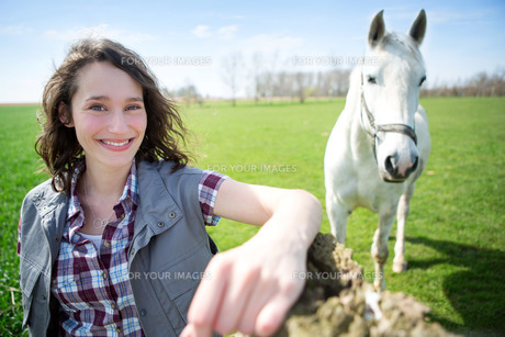 Portrait of a young attractive farmer in fields with horseの写真素材 [FYI00647081]