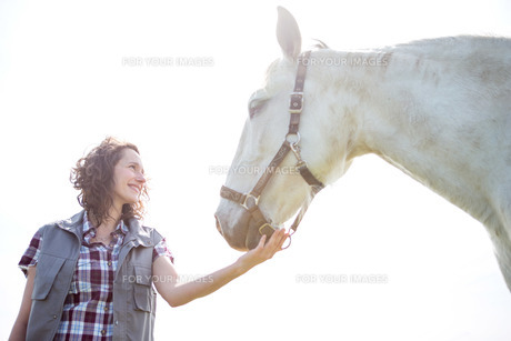 Portrait of a young attractive veterinary in fields with horseの素材 [FYI00647083]