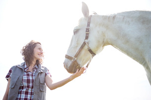 Portrait of a young attractive veterinary in fields with horseの写真素材 [FYI00647083]