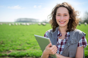 Young attractive farmer in a field using tabletの写真素材 [FYI00647088]