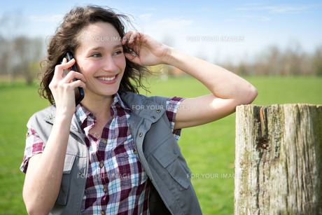 Young attractive farmer in a field using mobile phoneの素材 [FYI00647090]