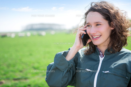 Young attractive farmer in a field using mobile phoneの写真素材 [FYI00647093]