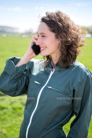 Young attractive farmer in a field using mobile phoneの素材 [FYI00647095]