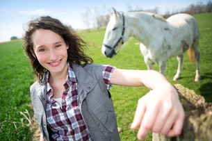 Portrait of a young attractive farmer in fields with horseの写真素材 [FYI00647096]