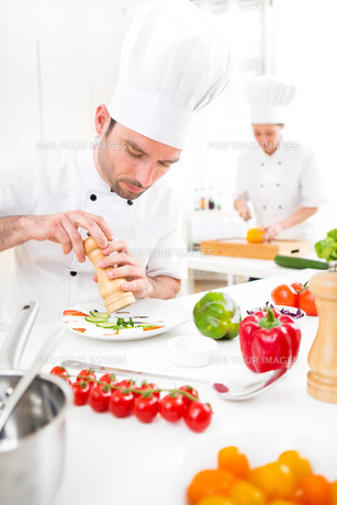 Young attractive professional chef cooking in his kitchenの写真素材 [FYI00647137]