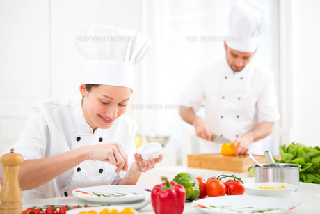 Young attractive professional chef cooking in his kitchenの写真素材 [FYI00647139]