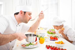 Young attractive professional chef tasting sauceの写真素材 [FYI00647168]