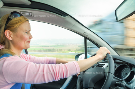 Attractive adult woman safe carefully driving car suburban roadの写真素材 [FYI00647212]