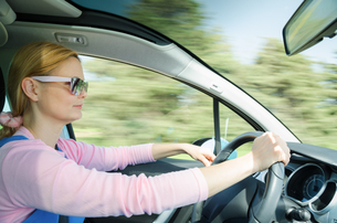 Pretty woman in sunglasses driving fast carの写真素材 [FYI00647229]
