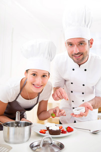 Young chef training a young attractive girl to cookの写真素材 [FYI00647323]