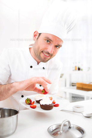 Young attractive professional chef cooking in his kitchenの写真素材 [FYI00647325]