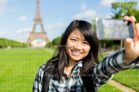 Young attractive asian tourist in Paris taking selfieの写真素材 [FYI00647427]