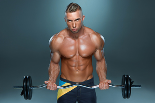 Portrait of super fit muscular young man working out in gym.の写真素材 [FYI00647428]