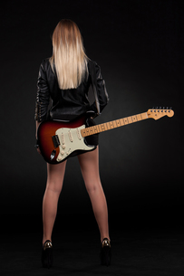 Beautiful young blonde dressed in black leather with electric guitarの写真素材 [FYI00647433]