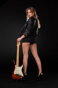Beautiful young blonde dressed in black leather with electric guitarの写真素材 [FYI00647435]