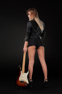 Beautiful young blonde dressed in black leather with electric guitarの写真素材 [FYI00647437]