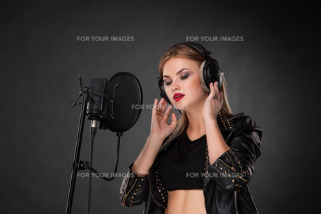 Portrait of a beautiful woman singing into microphone with headphones in studio on black backgroundの写真素材 [FYI00647447]