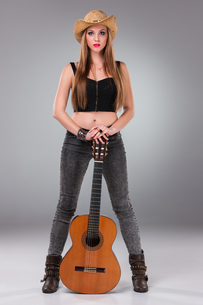 The beautiful girl in a cowboy's hat and acoustic guitar.の写真素材 [FYI00647457]
