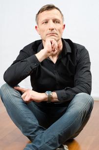 Portrait denkender Mann auf dem Boden sitzendの写真素材 [FYI00647528]