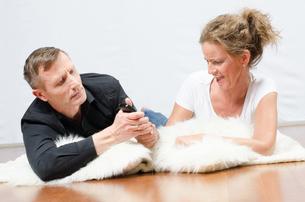 Mann und Frau streiten sich um TV Fernbedienungの写真素材 [FYI00647532]