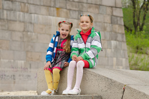 Two girls sit on a granite staircaseの写真素材 [FYI00647665]