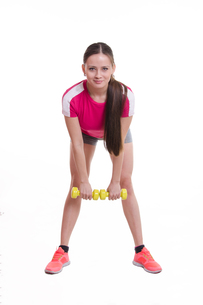 The athlete performs a forward bends with dumbbellsの写真素材 [FYI00647674]