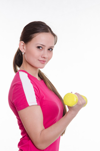 Sportswoman with dumbbells inflates his right handの写真素材 [FYI00647684]