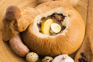 traditional white borscht (zurek) with sausage,egg and mushrooms in bread as bowlの写真素材 [FYI00647845]