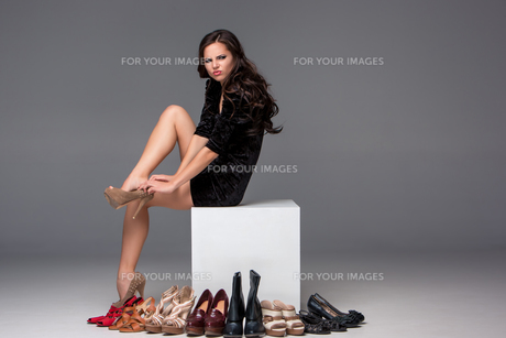 picture of sitting woman trying on high heeled shoesの写真素材 [FYI00647916]