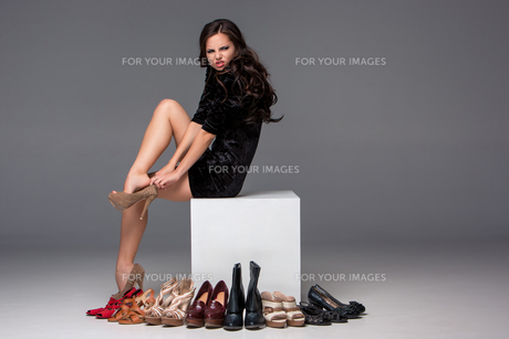 picture of sitting woman trying on high heeled shoesの写真素材 [FYI00647917]